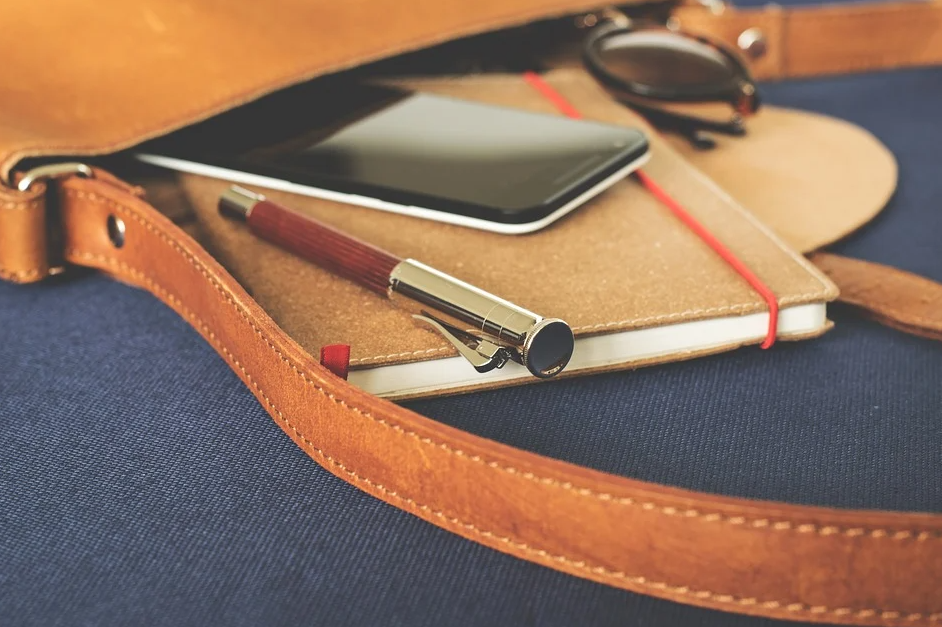 kabelka s telefonem a zápisníkem